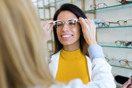 Close-up of young ophthalmologist putting on eyeglasses on smiling beautiful woman in optic shop.