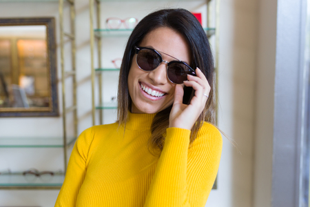Portrait of beautiful young woman showing her new sunglasses while looking at camera in optic shop. Stock Photo