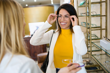 Shot of smiling beautiful woman choosing and showing eyeglasses to attractive young oculist in optic shop. Stock fotó