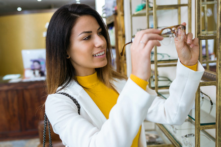 Shot of beautiful young woman deciding for eyeglasses of different shapes and colors in optic shop. Stock Photo