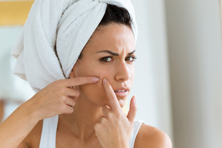 Shot of beautiful young woman removing pimple from her face in a bathroom home. Stockfoto