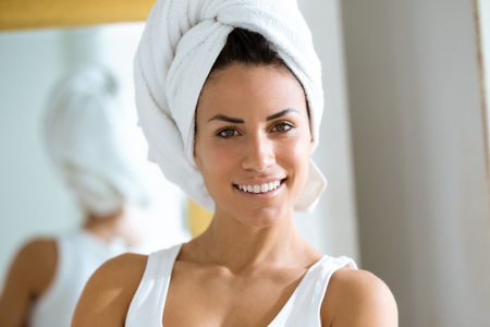 Portrait of attractive young woman wrapped a towel around head  in her bathroom at home.
