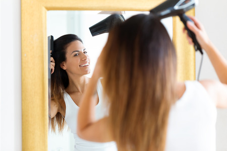 Shot of beautiful young woman blow drying her hair near the mirror in the bathroom.