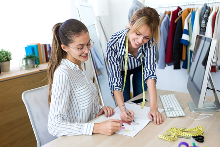 Shot of two young fashion designers deciding on the designs of the new collection of clothes in the sewing workshop.