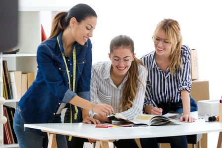 Shot of group of fashion designers working and deciding details of new collection of clothes in the sewing workshop. Stock Photo