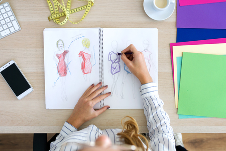 Close-up of young fashion designer drawing a few sketches in sewing workshop.