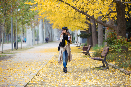 Shot of pretty young woman using her mobile phone while walking through the park during autumn.