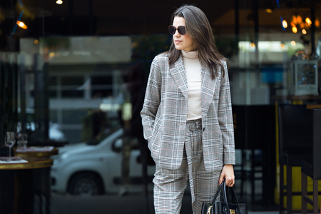 Shot of stylish young beautiful businesswoman posing in the street outside the coffee shop.