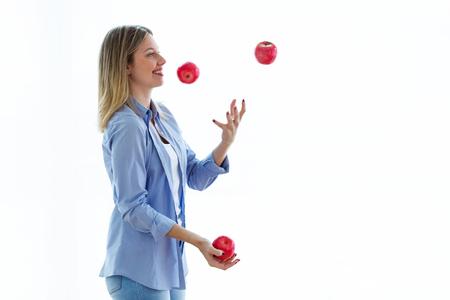 Coup de jolie jeune femme jonglant avec des pommes rouges sur fond blanc. Banque d'images