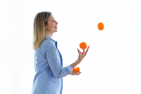 Coup de jolie jeune femme jonglant avec des oranges sur fond blanc.