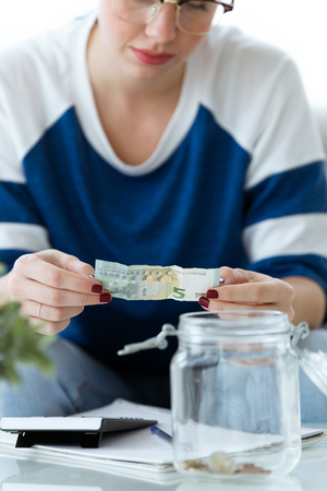 Shot of worried young woman looking her savings while sitting on sofa at home.