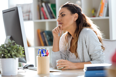 Shot of pretty young business woman eating yogurt while working with computer in the office.