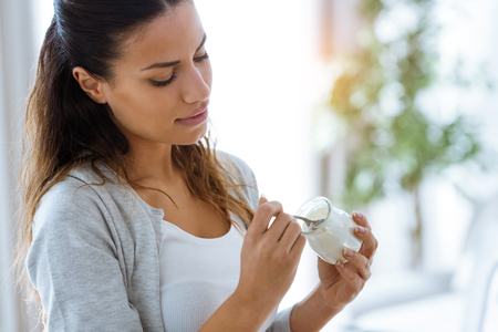 Aufnahme einer hübschen jungen Frau, die zu Hause Joghurt isst.