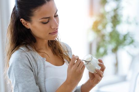 Foto de mujer joven y bonita comiendo yogur en casa.