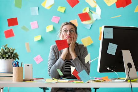 Shot van een gestresste jonge zakenvrouw die opkijkt omringd door post-its op kantoor. Stockfoto