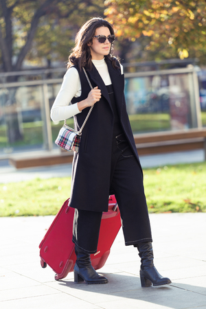 Shot of pretty young woman walking with suitcase to the train station.