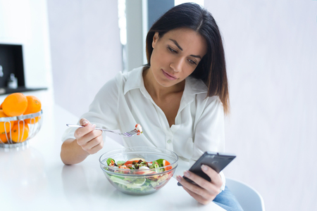 Foto de mujer joven y bonita con su teléfono móvil mientras come ensalada en la cocina de casa. Foto de archivo