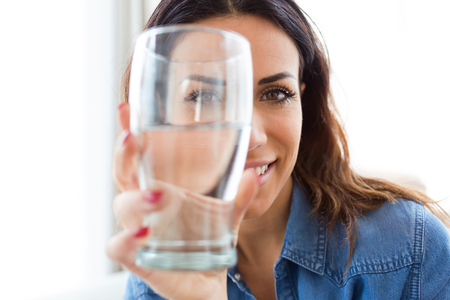 Portrait of pretty young woman smiling while looking at the camera through the glass of water at home.