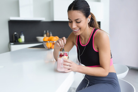 Shot of sporty young woman eating strawberry smoothie while listening to music in the kitchen at home.