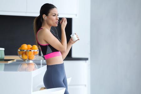 Foto de mujer joven deportiva escuchando música con teléfono móvil mientras come yogur en la cocina de casa. Foto de archivo
