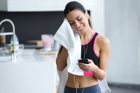 Shot of sporty young woman using her mobile phone while drying the sweat with a towel at home.