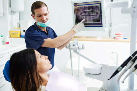 Shot of attractive young dentist showing to his patient radiography of her mouth in the dental clinic.