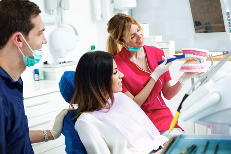 Shot of beautiful dentist explaining how to brush teeth correctly to a patient in a clinic box with medical equipment. Фото со стока
