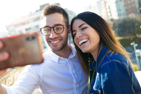 Shot of lovely attractive smiling couple taking selfie with their mobile phone in the street.