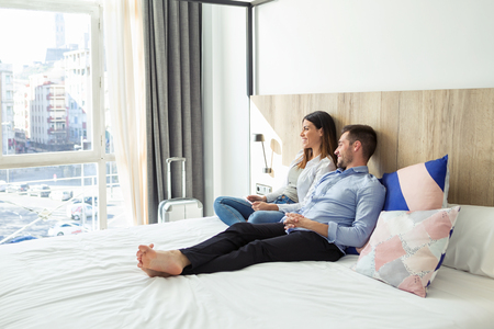 Shot of beautiful lovely young couple lying and relaxing on bed looking sideways at hotel room.