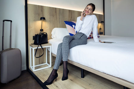 Shot of stylish young businesswoman talking with her mobil phone sitting on the bed at hotel room.