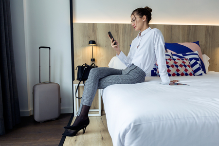 Shot of beautiful young businesswoman texting with her mobil phone sitting on the bed at hotel room.