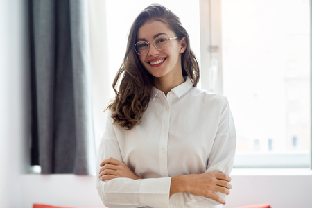 Portrait if beautiful smiling businesswoman with eyeglasses looking at the camera in the hotel room.
