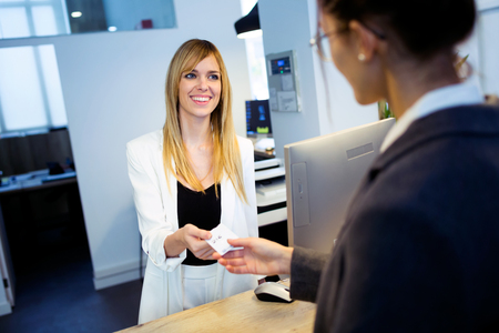 Shot of attractive female recepcionist giving room key card to client in hotel.