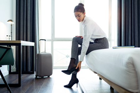 Shot of pretty businesswoman taking off high heels shoes after work at her hotel room. 스톡 콘텐츠