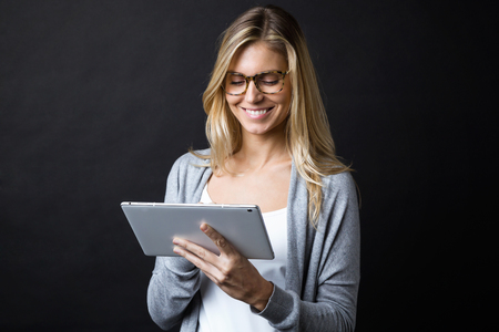 Shot of smiling beautiful young woman with eyeglasses working with digital tablet over black backgound.