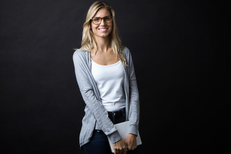 Portrait of smiling beautiful young woman with eyeglasses holding digital tablet while looking at the camera over black backgound. Imagens
