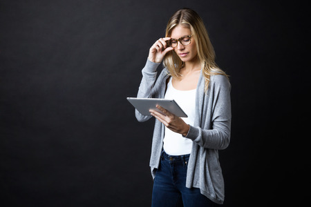 Shot of concentrated beautiful young woman with eyeglasses working with digital tablet standing over black backgound.