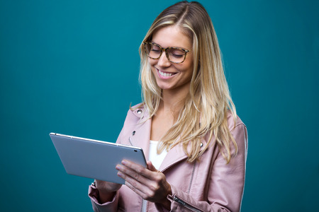 Shot of smiling beautiful young woman with eyeglasses working with digital tablet over blue backgound.