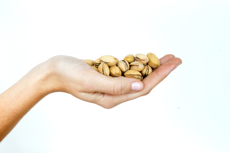 Young woman hand holding pistachios on isolated white background.