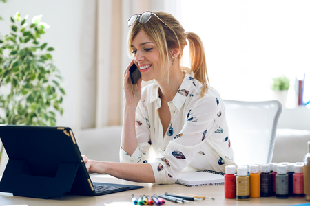 Shot of smiling beautiful young designer woman working with her digital tablet while talking with her mobile phone at the office.