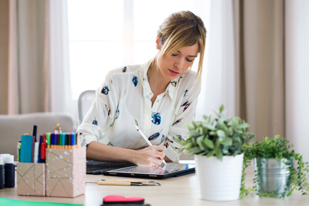 Shot of concentrated beautiful young designer woman drawing something on her digital tablet at the office. Stock Photo