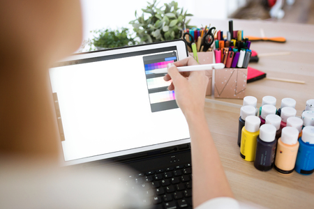 Close-up of young designer woman hand working with her digital tablet at the office.