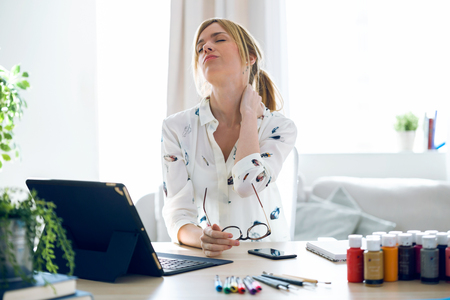 Shot of fatigued young woman with neck pain working with her digital tablet at the office. Stockfoto - 119079604