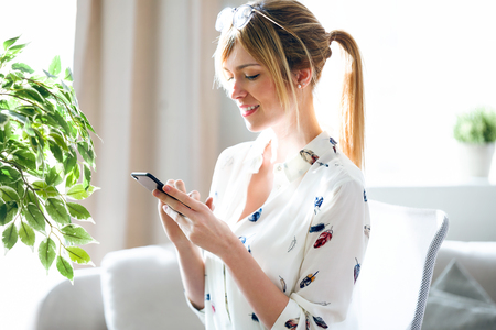 Shot of charming beautiful young designer woman texting with her mobile phone at the office. Stock Photo