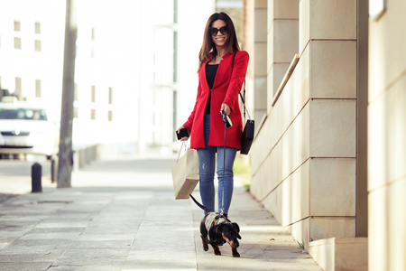 Shot of cool beautiful young woman walking while shopping for the city with her little dog. 写真素材