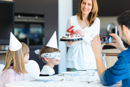 Shot of cute family celebrating childrens birthday while parents covering sons eyes in the kitchen at home.
