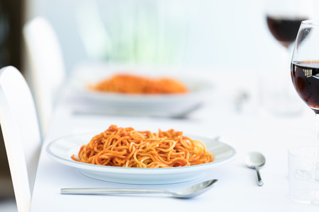 Close-up of delicious spaghetti with tomato sauce served on a white plate on the kitchen at home.
