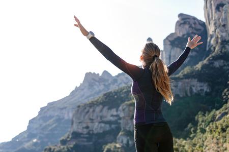 Foto de corredor de pista con los brazos abiertos levantados mientras disfruta de la naturaleza en la cima de la montaña.