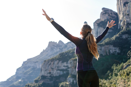 Shot of trail runner with open arms raised while enjoying nature on mountain peak. Stockfoto