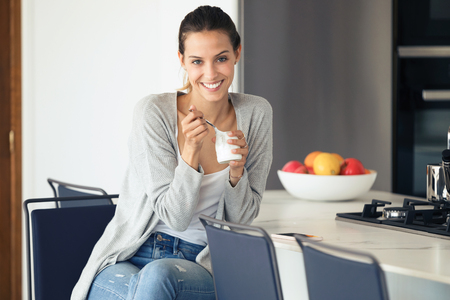 Portrait of pretty young woman looking at camera while eating yogurt in the kitchen at home. Standard-Bild - 121569958